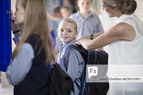 Lehrerin hilft Schülerin mit Rucksack auf dem Flur