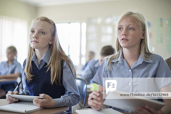 Two schoolgirls in classroom with digital tablets