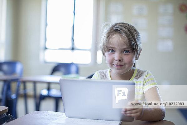 Porträt einer lächelnden Grundschülerin mit digitalem Tablett Porträt einer lächelnden Grundschülerin mit digitalem Tablett