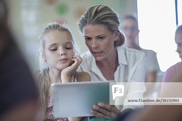 Lehrerin mit digitalem Tablett im Gespräch mit Schülerin im Klassenzimmer