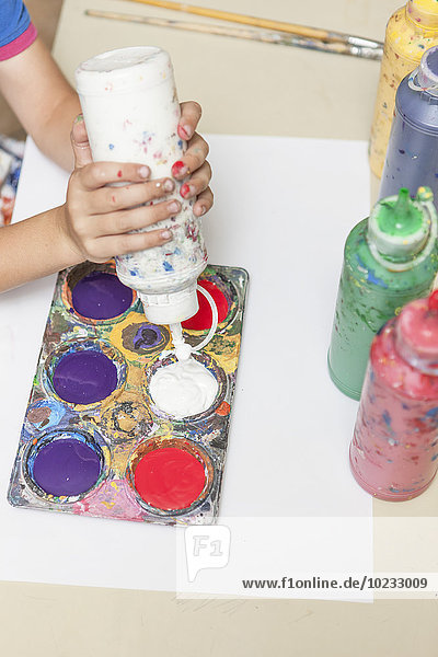 Knabenhandpress-Farbflasche in einer Kunstklasse Knabenhandpress-Farbflasche in einer Kunstklasse