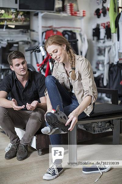 Junge Frau beim Kauf von Fahrradschuhen  Verkäuferberatung