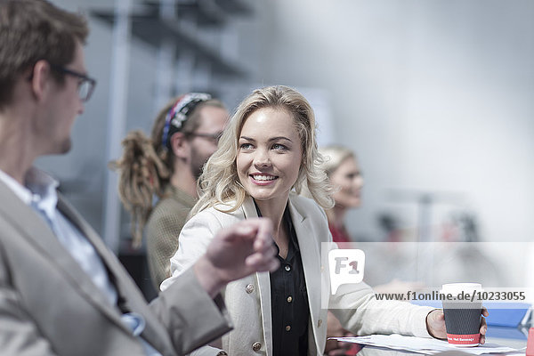 Portrait of smiling young woman face to face with a colleague in a meeting