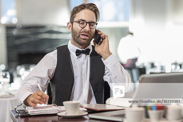 Restaurantmitarbeiter am Tisch mit Laptop und Handy