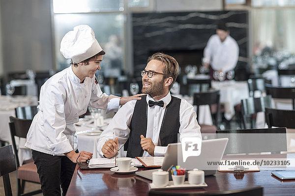 Restaurantchef und Manager besprechen Reservierungen