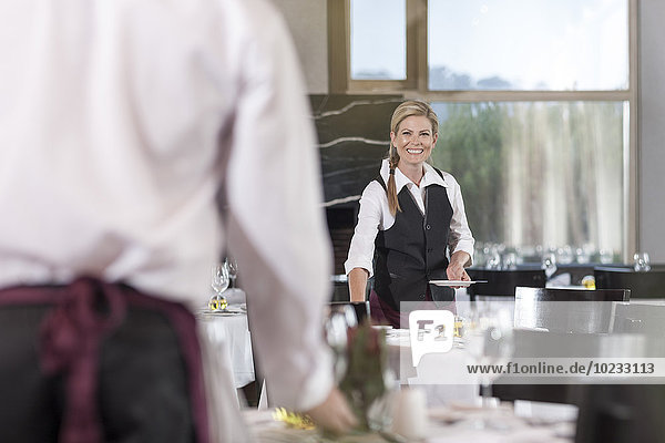 Restaurantmitarbeiter decken Tische