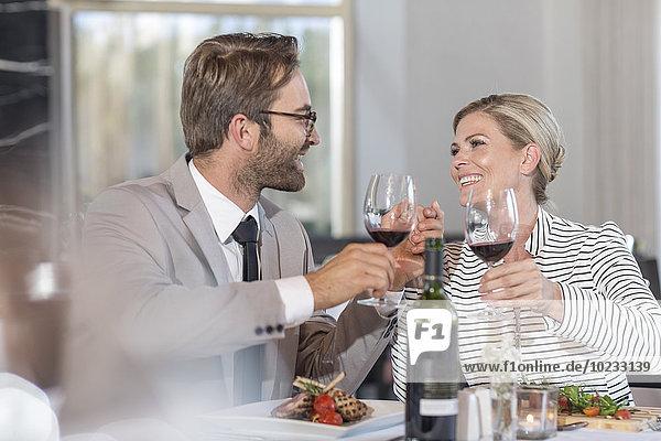 Mittleres erwachsenes Paar im Restaurant Toasting mit Rotwein