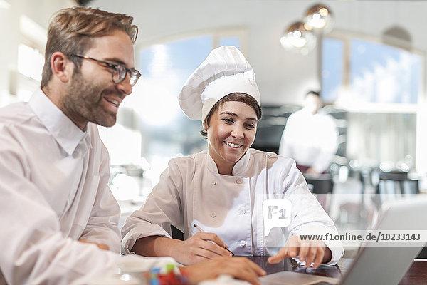 Restaurantchef und Manager diskutieren über das Menü