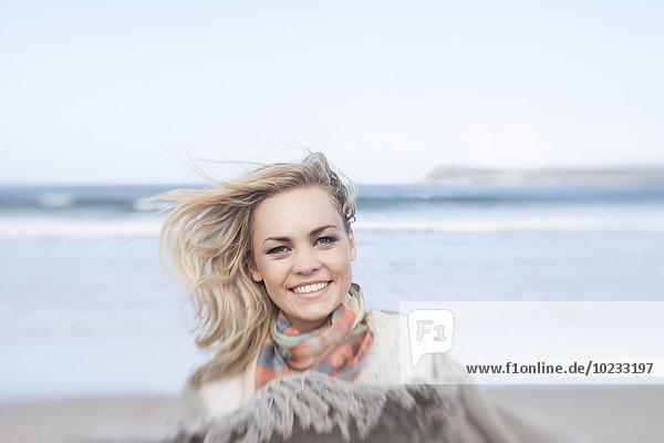 Südafrika  Kapstadt  Porträt einer lächelnden jungen Frau vor dem Meer