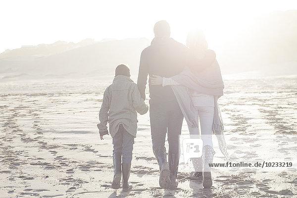 Südafrika  Kapstadt  Rückansicht der Familie am Strand bei Gegenlicht