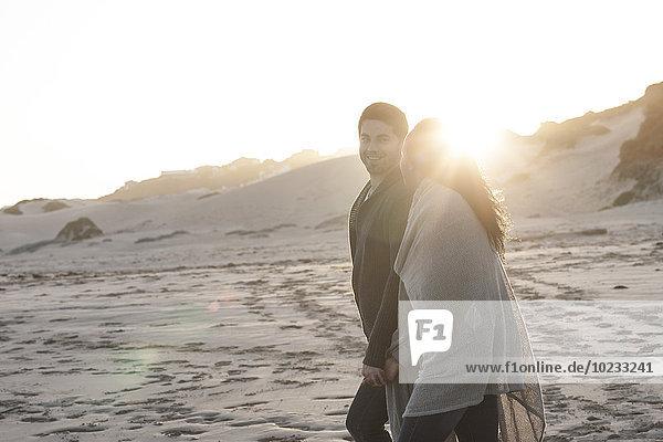 Südafrika  Kapstadt  junges Paar bei Sonnenuntergang am Strand spazieren gehen