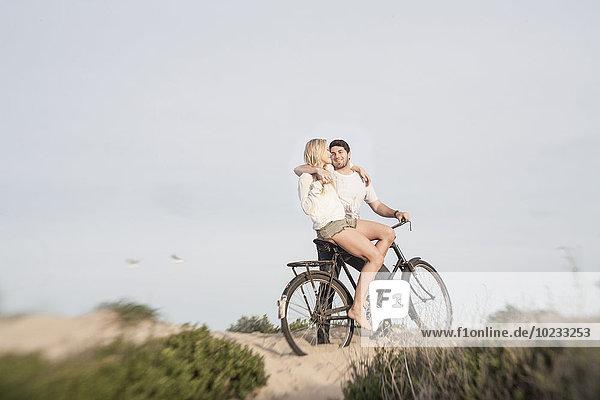 Junges Paar mit Fahrrad auf einer Stranddüne stehend