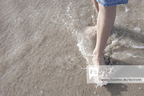Junge mit den Füßen im Meer stehend