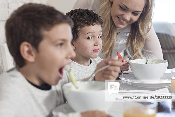 Junge mit Familie beim Mittagessen im Speisesaal,  der sich weigert,  gesund zu essen.
