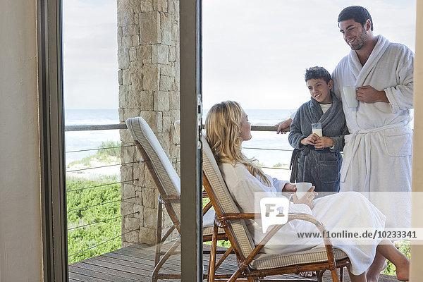 Familie im Bademantel auf der Terrasse des Strandhauses