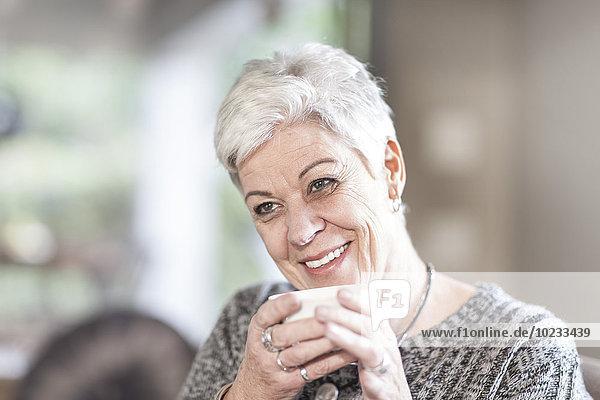 Porträt einer weißhaarigen Seniorin mit Tasse