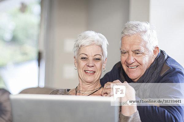 Seniorenpaar schaut zusammen auf den Laptop