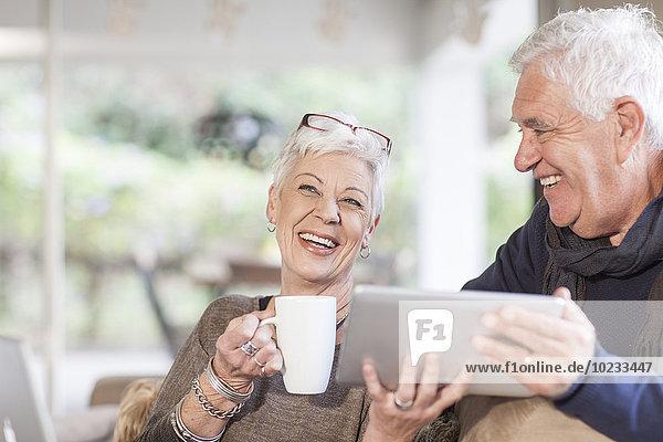 Seniorenpaar mit digitalem Tablett und Tasse Kaffee