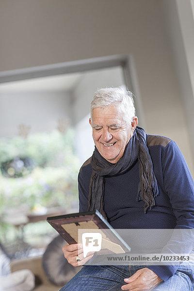 Älterer Mann beim Betrachten des Bilderrahmens