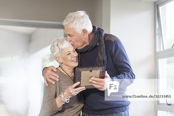 Seniorenpaar mit Bilderrahmen zu Hause