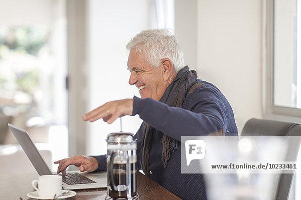 Senior Mann mit Laptop und Kaffeekanne zu Hause