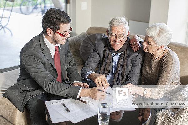 Seniorenpaar zu Hause bei einem Treffen mit dem Verkäufer