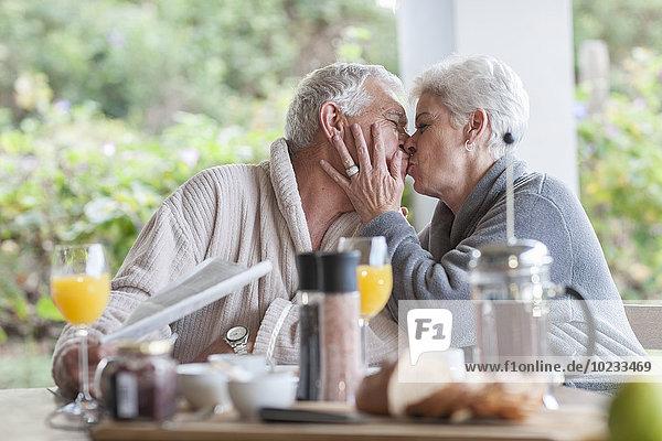 Ein älterer Mann küsst ihren Mann am Frühstückstisch.