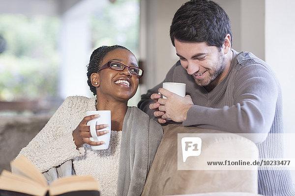 Junges Paar mit Kaffeetassen zu Hause
