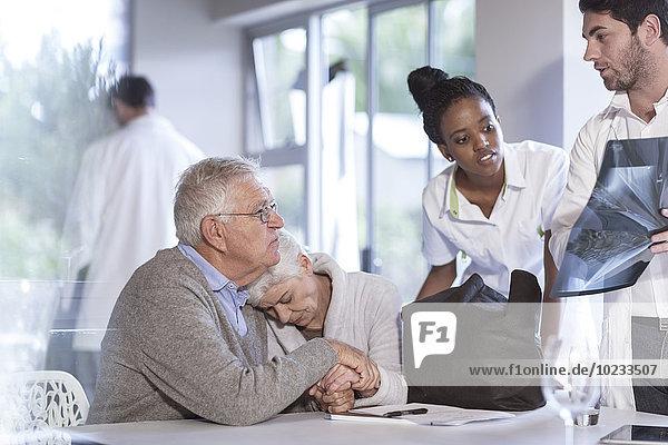 Traurige Seniorin mit Ehemann in der Klinik im Gespräch mit Arzt und Krankenschwester