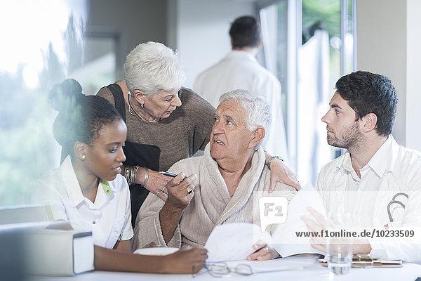Seniorenpaar in der Klinik mit Arzt und Krankenschwester