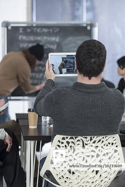Lässiger Geschäftsmann beim Fotografieren mit digitalem Tablett auf einem Meeting
