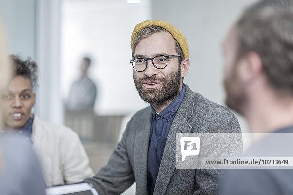 Mann mit Brille und gelber Mütze im Gespräch mit Kollegen