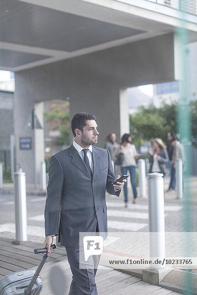 Geschäftsmann mit Koffer und Smartphone