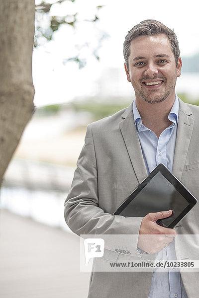 Porträt eines lächelnden Geschäftsmannes mit digitalem Tablett