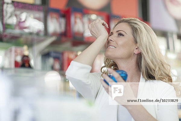 Woman in drugstore smelling new fragrance