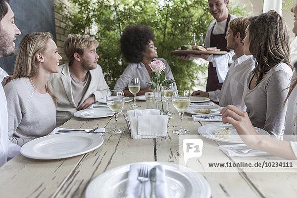 Freunde beim gemeinsamen Mittagessen im Restaurant  draußen sitzend