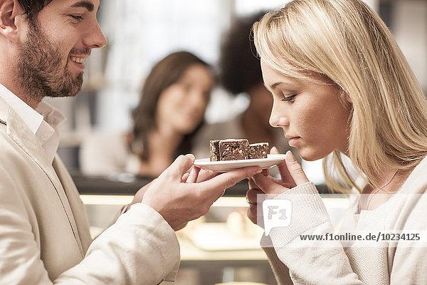 Mann hält Teller mit Gebäck  Frau riecht Geschmack