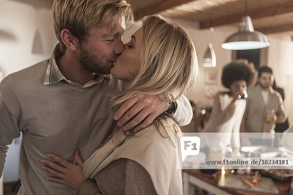 Young couple kissing in kitchen with friends in background