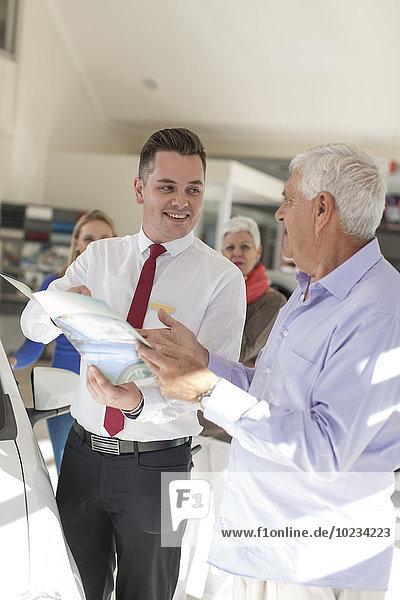 Senior im Gespräch mit dem Autohändler