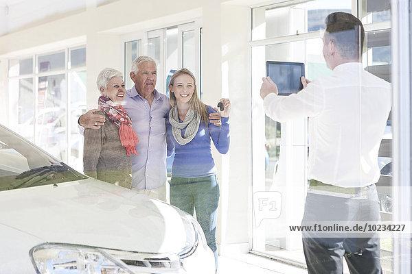 Autohaus fotografiert glückliche Familie mit Autoschlüssel
