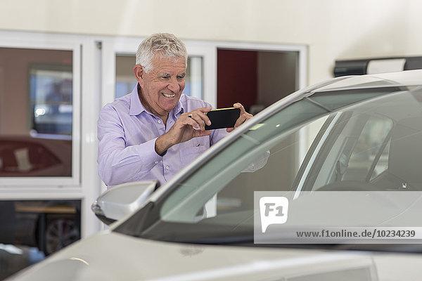 Senior Mann beim Fotografieren eines neuen Autos im Showroom