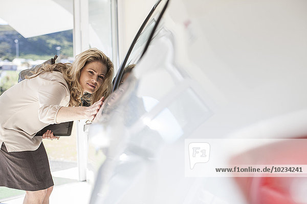 Woman looking at a new car in showroom