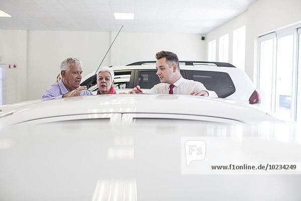Autohändler zeigt neues Auto dem älteren Paar im Showroom