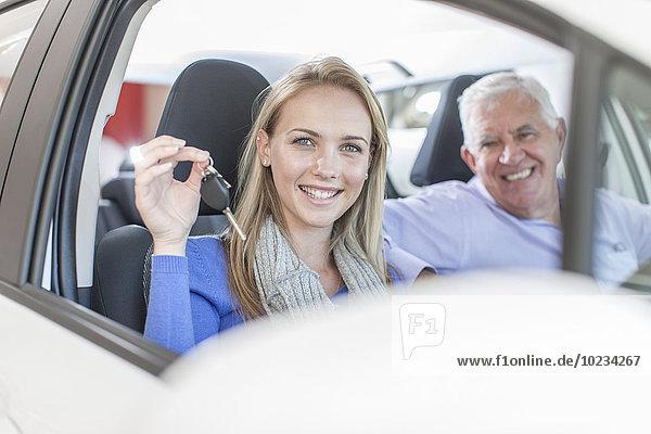 Porträt einer lächelnden Frau mit Schlüssel im neuen Auto