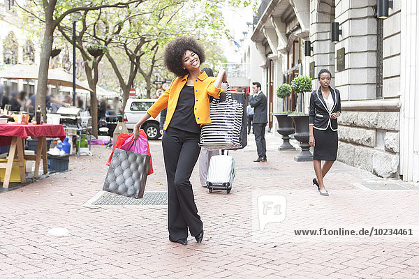 Happy young woman posing with her shopping bags on pavement