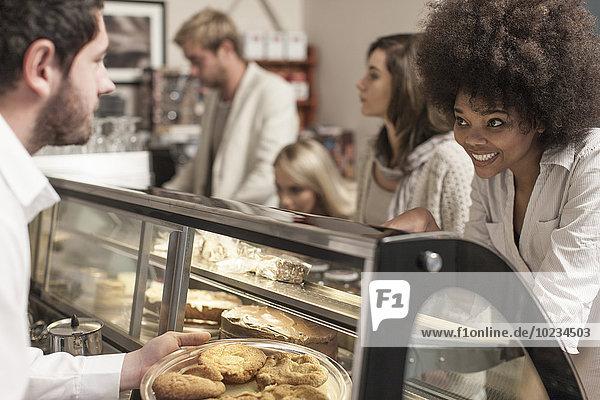 Junge Frauen wählen Kuchen aus der Kuchentheke im Coffee-Shop