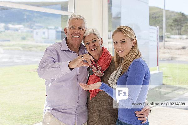 Vater gibt seiner Tochter Schlüssel für ein neues Auto