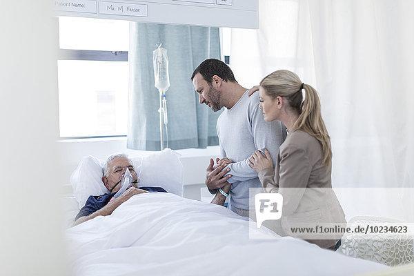 Ehepaar zu Besuch bei einem älteren Patienten im Krankenhaus