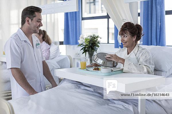 Krankenschwester  die den Patienten beim Mittagessen beobachtet.