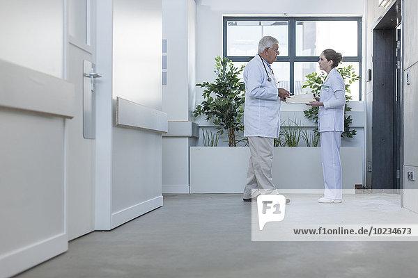 Arzt und Krankenschwester im Krankenhausflur im Gespräch